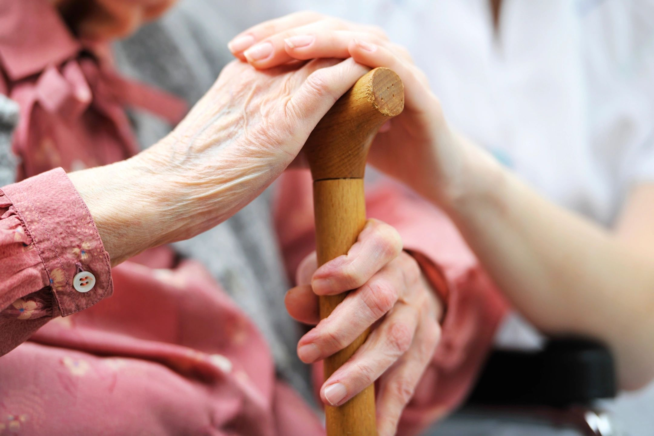 Older woman hand on cane